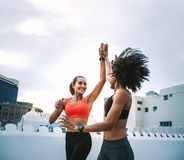 Cheerful fitness women giving high five while jogging on rooftop. Two cheerful women in fitness wear giving high five while running on the terrace. Women stock photos