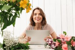Cheerful florist lady standing with flowers using laptop computer. Stock Images