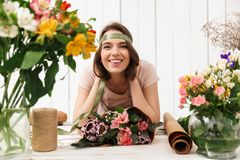 Cheerful florist woman with flowers in workshop. Photo of cute cheerful florist woman standing near table working with flowers in workshop. Looking camera Royalty Free Stock Image