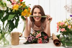 Cheerful florist woman with flowers in workshop. Photo of cute cheerful florist woman standing near table working with flowers in workshop. Looking camera Royalty Free Stock Images