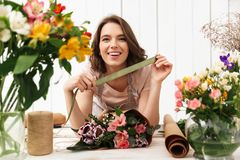 Cheerful florist woman with flowers in workshop. Photo of cute cheerful florist woman standing near table working with flowers in workshop. Looking camera Royalty Free Stock Photos