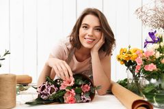 Cheerful florist woman with flowers in workshop. Photo of cute cheerful florist woman standing near table working with flowers in workshop. Looking camera Stock Photography