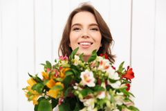 Cheerful florist woman standing with flowers. Young cheerful florist woman standing with flowers and looking camera in workshop Royalty Free Stock Photography