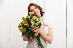 Cheerful florist woman standing with flowers. Young cheerful florist woman standing with flowers and looking camera in workshop Stock Photo