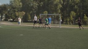 Cheerful footballers celebrating a goal on pitch. Young street football team attacking opponent goal, moving forward with passes and scoring a goal during soccer stock video