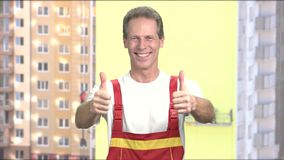 Cheerful foreman gesturing with two thumbs up. Happy middle-aged manual worker posing on constructions background. Positive european builder stock video footage