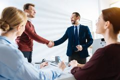 Cheerful four colleagues celebrating great deal stock image