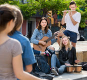 Cheerful four friends with musical instruments. Cheerful four friends teenagers with musical instruments together outdoors Stock Photo