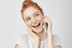 Cheerful foxy girl rejoicing listening music in headphones smiling. Royalty Free Stock Image