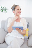 Cheerful fresh model in white clothes using tablet pc Royalty Free Stock Photos