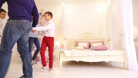 Cheerful and friendly family leads around circle in bedroom with Christmas tree day. Adult attractive parents and two children, twin brothers joined hands and stock video footage