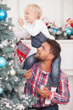 Cheerful friendly family is preparing for. Handsome young men is helping his son to decorate New Year tree. He is holding the child on his shoulders and smiling royalty free stock photo