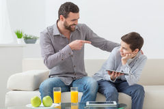 Cheerful friendly family is spending time together. Cute father and son are talking and smiling. They are sitting on the couch at home. The boy is using a tablet Royalty Free Stock Photography