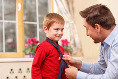 Cheerful friendly family is spending time together. Handsome young father is helping his son to wear the tie. They are looking at each other and smiling stock photography