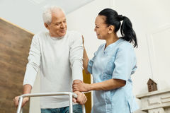 Cheerful friendly nurse helping the elderly man. One more step. Cheerful positive friendly nurse standing near the elderly men and helping him to move around Stock Image