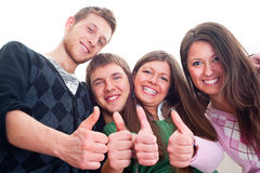 Cheerful friends. Four cheerful friends showing thumbs up over white background Royalty Free Stock Photos