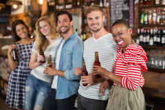 Cheerful friends with beer bottles at pub. Portrait of cheerful friends with beer bottles at pub Royalty Free Stock Photos