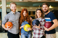 Cheerful friends bowling together Royalty Free Stock Images