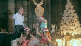 Cheerful Friends at Christmas party having fun, playing with confetti at the party. stock video footage