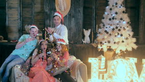 Cheerful Friends at Christmas party. Sparkles of fireworks, confetti flying in the air at the party. stock footage
