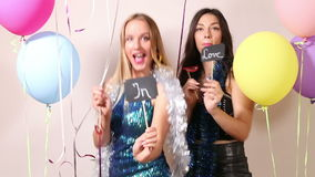 Cheerful friends dancing with a sign in love in party photo booth stock video footage
