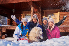 Cheerful friends with dog spend winter holidays together at mountain cottage. Stock Photography