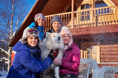 Cheerful friends with dog spend winter holidays together at mountain cottage Royalty Free Stock Photo