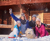 Cheerful friends with dog spend winter holidays together at mountain cottage Stock Photo