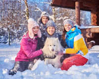 Cheerful friends with dog spend winter holidays together at mountain cottage Stock Image