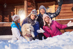 Cheerful friends with dog spend winter holidays together at mountain cottage Stock Images