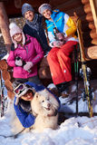 Cheerful friends with dog spend winter holidays together at mountain cottage Royalty Free Stock Photography