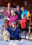 Cheerful friends with dog spend winter holidays together at mountain cottage Stock Photography