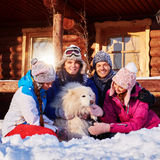 Cheerful friends with dog spend winter holidays together at mountain cottage Stock Photos