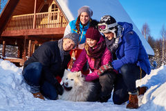 Cheerful friends with dog spend winter holidays together at mountain cottage Royalty Free Stock Photos