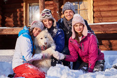 Cheerful friends with dog spend winter holidays together at mountain cottage Royalty Free Stock Image