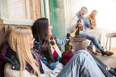 Cheerful friends drinking beer on porch. Side view of cheerful friends drinking beer on porch Stock Photos
