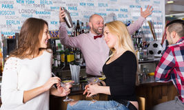 Cheerful friends drinking and chatting Royalty Free Stock Images