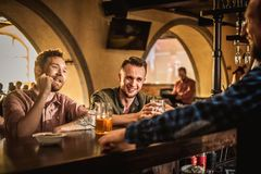 Cheerful friends drinking draft beer in a pub.  stock images