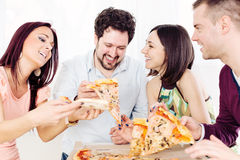 Cheerful friends eating pizza. Group of happy friends sitting and eating pizza at Home Interior royalty free stock photo