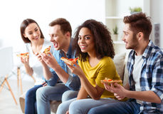 Cheerful friends eating pizza Stock Photos
