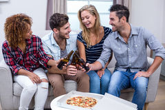 Cheerful friends enjoying beer and pizza Royalty Free Stock Photos