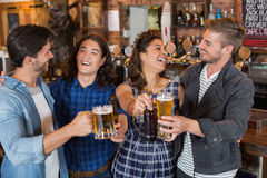 Cheerful friends enjoying in pub. Cheerful friends tossing beer glasses and bottles in pub Stock Photos