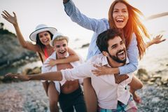 Cheerful friends enjoying weekend and having fun on beach royalty free stock photography