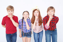 Cheerful friends expressing positivity. Keep silence. Agreeable children standing together and holding fingers on the mouths royalty free stock photos