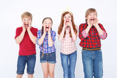 Cheerful friends expressing positivity. Screaming out loud. Upbeat children standing together and holding their hands on their faces while screaming stock photography