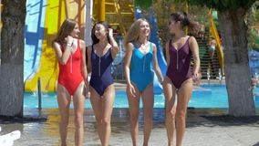 Cheerful friends girls into bathing suits have fun at aquapark on background colored waterslides on holiday
