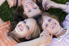 Cheerful friends girls laying in grass together. Selective focus stock photo