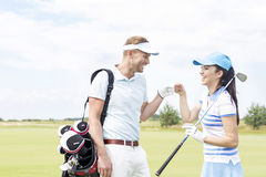 Cheerful friends giving high-five at golf course Royalty Free Stock Photo