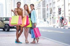 Cheerful friends go to the store. Three girlfriend holding shopp Stock Photo