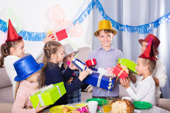 Cheerful friends handing gifts to birthday boy. During dinner Royalty Free Stock Image